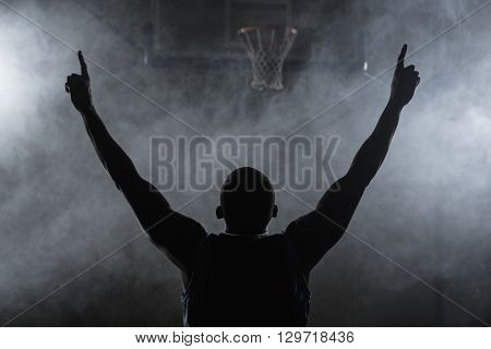 Rear view of a basketball player with his arms in the air in a gymnasium