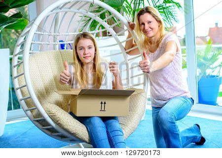 Girl And Her Mother Opening A Package Together And Showing Thumb Up