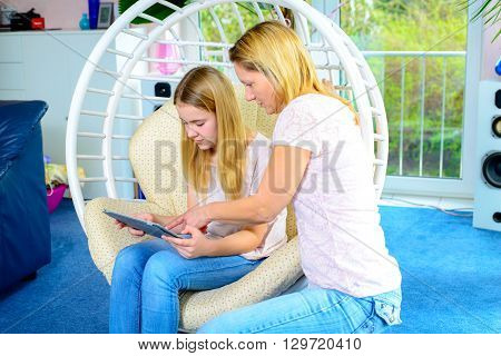 Mother And Her Daughter Using Tablet Computer Together