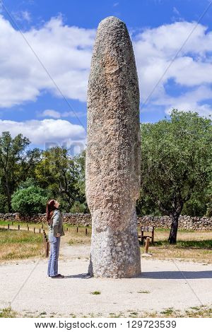 Castelo de Vide, Portugal - April 26, 2015: Woman looking at the Standing Stone / Menhir of Meada, the largest of the Iberian Peninsula. A mysterious phallic prehistoric fertility monument.