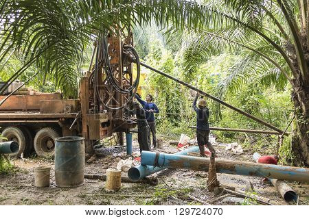 NAKHON SI THAMMARAT THAILAND - DECEMBER 7: Men working a drilling rig to a water well for crop irrigation on December 7 2015 in Nakhon Si Thammarat Thailand.