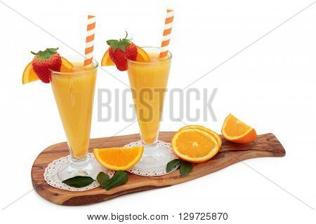 Orange fruit juice drink in glasses with fresh strawberries, striped straws on an olive wood board over white background. High in vitamins, anthocyanins and antioxidants.