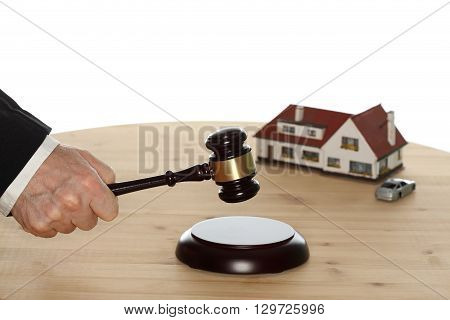 auctioneer with gavel in hand and house in background
