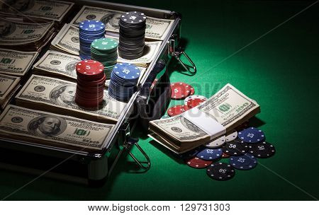 Case with dollars and chips on a green cloth background