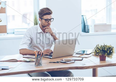 Confident expert at work. Pensive young handsome man using his laptop while sitting at his working place