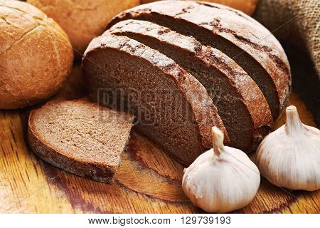 Three loaves of bread and garlic on cutting board