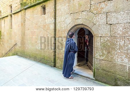 Mont St. Michel France - May 22 2012: Normandy a monk in front of a door of a house in the ascent to the abbey