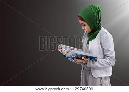 Image of asian muslim woman reading koran