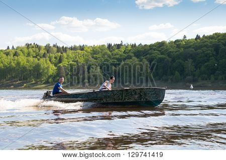 funny family riding  hand motorboat in lake