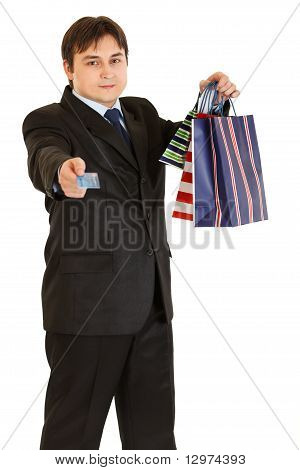 Smiling young businessman with shopping bags giving credit card isolated on white