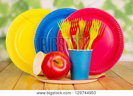 Bright, disposable tableware on abstract green background