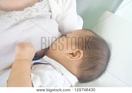 Asian mother breastfeeding her cute baby boy poster
