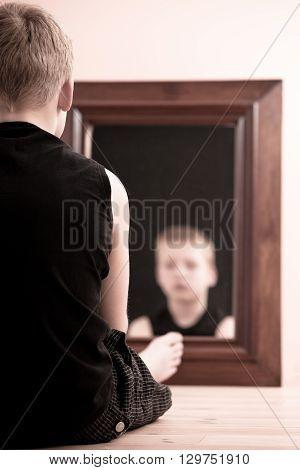 Child Sitting On Floor Staring Into Mirror