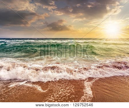 Sea ​​waves Crashing On Sandy Beach At Sunset