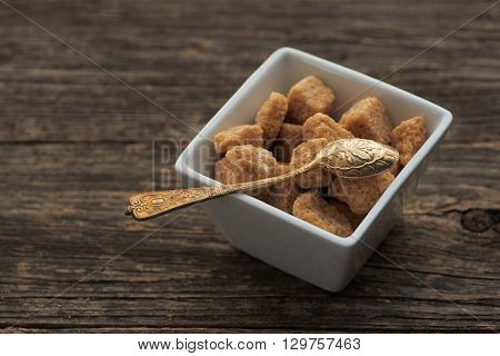 brown cane sugar on old wooden background