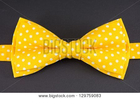 Yellow bow tie on black wooden table