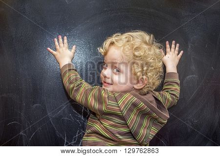 Little boy with curly hair at the old black school board