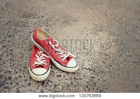 Red shoes on the floor of cement.