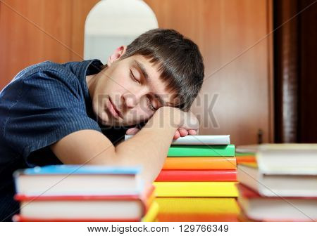 Tired Young Man sleep on the Books at the Home