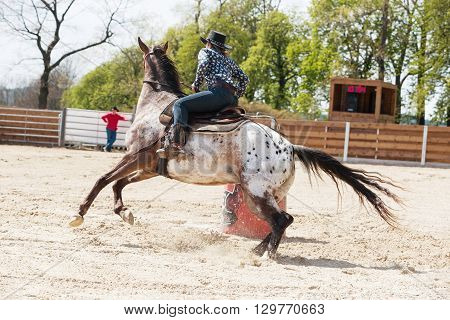 Young cowgirl riding a beautiful paint horse in a barrel racing event at a rodeo in Mitrov Czech republic