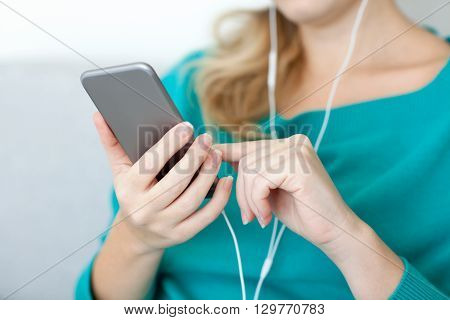 Woman holding a phone and listening to music on headphones