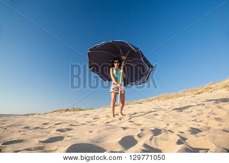 mini skirt and shirt brunette summer vacation woman looking sunglasses with open blue parasol in sand dune with blue sky in Palmar beach in Vejer Cadiz Andalusia Spain Europe poster