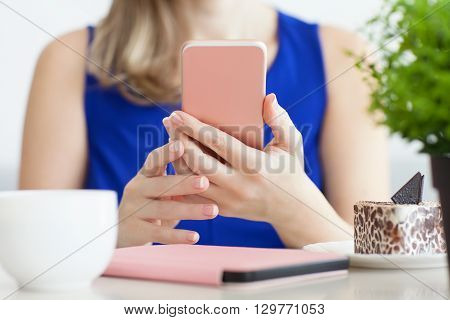 woman in a blue dress in the cafe holding a pink phone