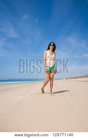 brunette summer vacation woman with sunglasses white shirt and green shorts standing gesturing sticking out tongue on sand with ocean in Zahara beach Cadiz Andalusia Spain Europe