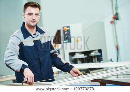 Plastic window and door manufacturing. Worker cutting PVC profile