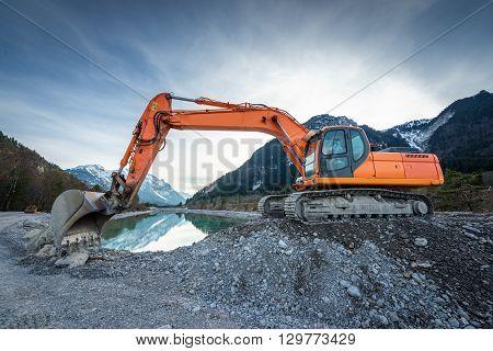 side view of orange shovel digger on gravel at lake and blue sky