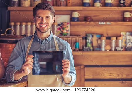 Handsome Young Waiter With Gadget