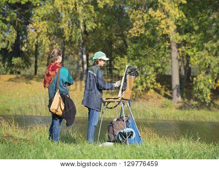 LENINGRAD REGION, RUSSIA - SEPTEMBER 24, 2015: The artist paints landscape september day