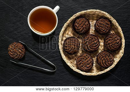 Chocolate mini cakes in a wicker basket tongs for pastries and a cup of tea on slate surface