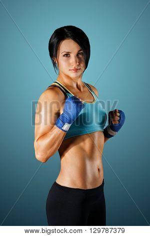 Young cute woman shows good fitness shape. Sporty strong body, girl in fitness wear shows biceps muscle. Slim brunette at grey background, studio portrait. Female body building. Fitness trainer.