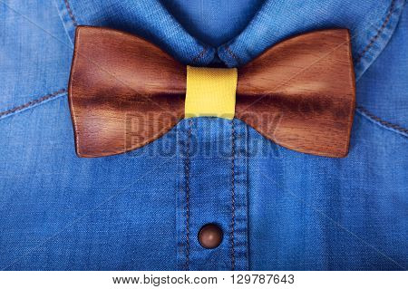 Men's casual blue jeans shirt with wooden yellow bow tie. Man accessories. Hipster style. Business background.