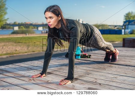 Fit woman doing full plank core exercise fitness training  working out outdoors