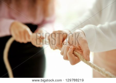 People hands pulling rope for playing tug of war closeup