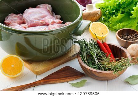 Raw rabbit meat with vegetables and herbs  in round ceramic pot on white wooden table surface