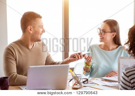 Pleasant interlocutor. Positive cheerful smiling colleagues sitting at the table and talking while working in the office together