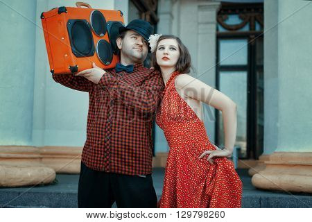 Man in a retro style he is holding a musical setting close to flirting woman.