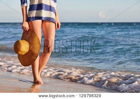 Woman walking by the sea with a sunhat in her hand, close up view