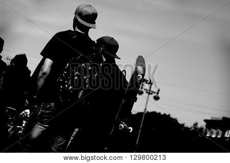 Two skateboarders in cap with bags and skatebords waiting contest. Black and white picture. Blank space for a text.