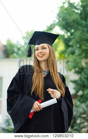 A graduate holding roll of white with red. Girl dressed in a black robe and an academic cap. She smiles