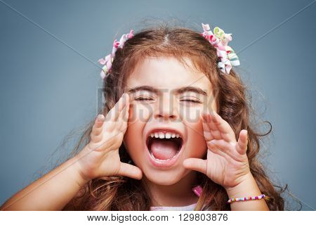 Portrait of a cute little baby girl screaming, naughty child yelling, expressing emotions, playful child rave about and making faces