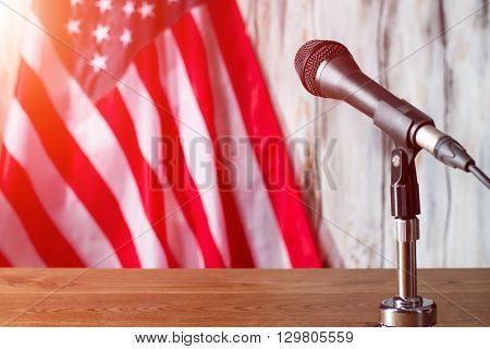 Microphone beside american flag. Banner behing table with microphone. Time to start the presentation. Voice of the people.