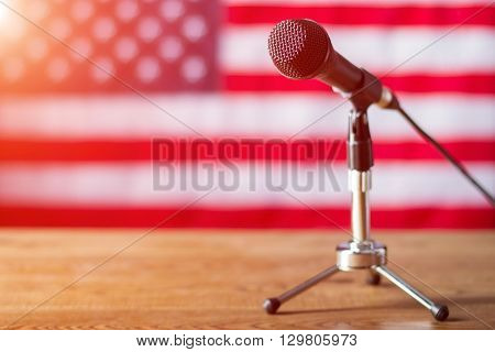 Microphone on US flag background. Table with microphone and banner. Radio show about to begin. Good morning, fellow citizens.