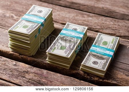 Dollar bundles on wooden background. Cash stacks of different size. Earned with hard labor. Money savings on old table.
