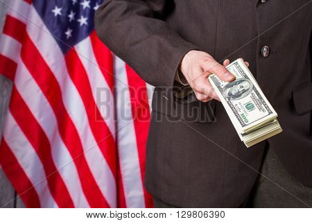 Businessman holding dollars beside flag. US flag, person and money. Our country our rules. I suggest you join us.