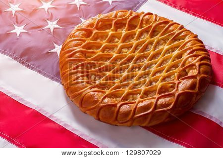 Pie laying on USA flag. Baked product and colorful banner. Time runs but traditions remain. Tasty dough and fresh apples.