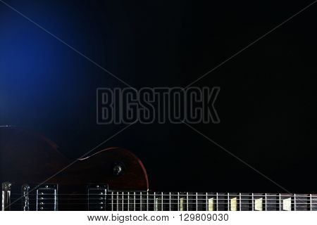 Brown electric guitar on dark background